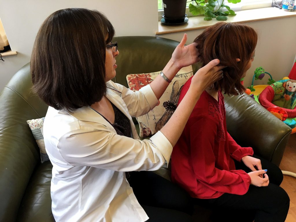 Jessica Jimison FNP-C checks Miranda Tsoumas PA-C for ticks by parting her hair so she can see the scalp
